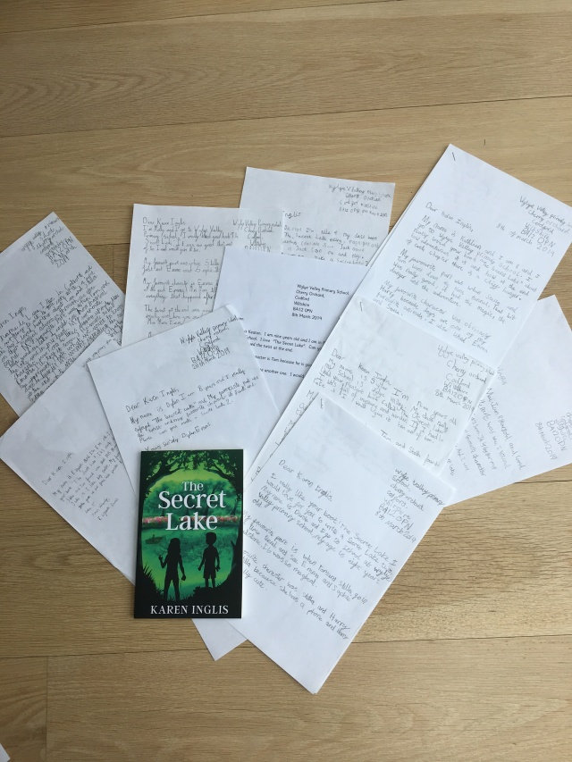 hand written letters arranged with a copy of The Secret Lake children's book