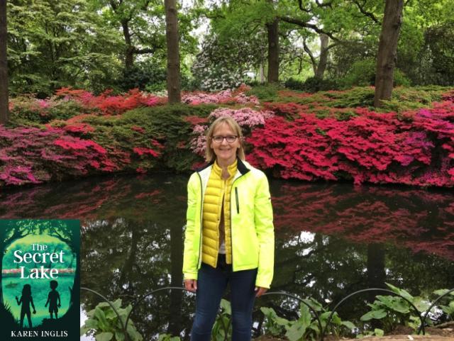 Karen Inglis standing in front of Still Pond lake with pin azaleis