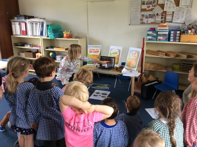 Karen Inglis author pointing to hedgehog video with nursery pupils in front