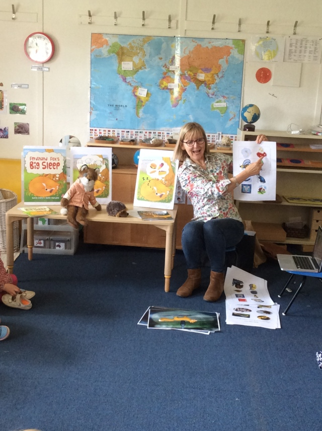 Karen Inglis at front of class holding up rhyming game images for pupils who are out of shot